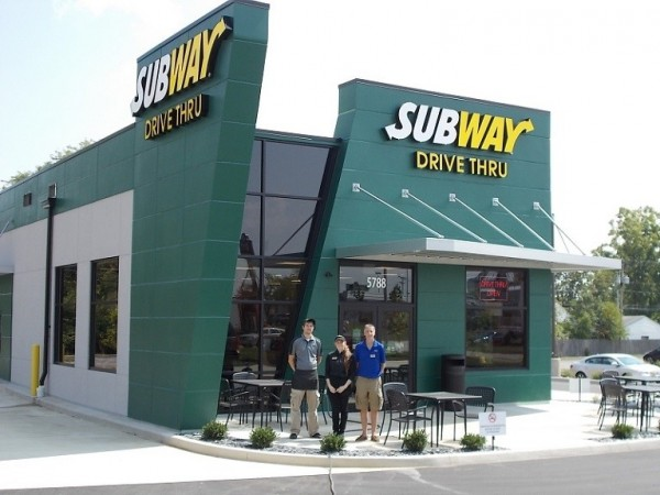Image of a subway restaurant with a dark green exterior and a drive thru, with 3 restaurant employees standing outside