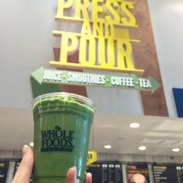 a green smoothie in a whole foods cup begin held up in front of a whole foods press and pour section