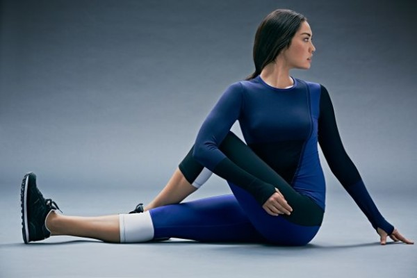woman in dark blue workout clothes stretching her back and legs by sitting on the floor and pushing her elbow against her knee with her elbow and twisting.