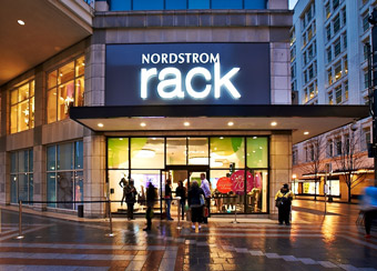 nordstrom rack store front at night. store is 2 stories tall and in a downtown area