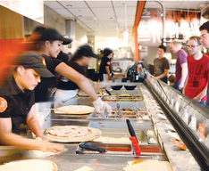 Employees adding toppings to pizzas for a line of customers.