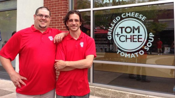 two men in red polos outside of tom+chee store front
