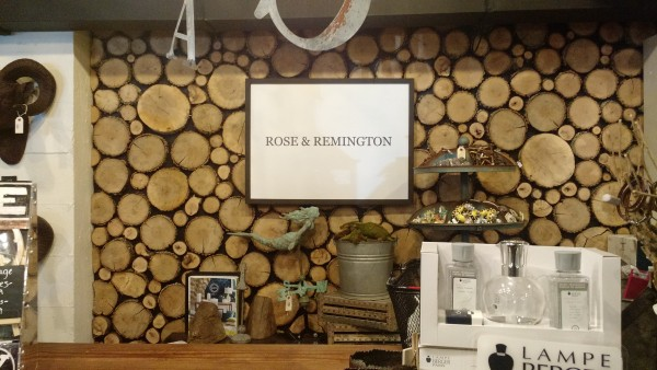 Inside store with a large picture of stacked logs on a wall behind a counter. .