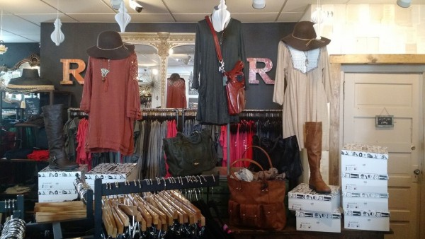 inside of rose and remington store with clothing on display in shades of dark red, gray, and tan