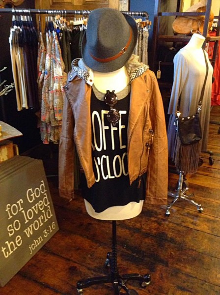 "a mannequin displaying a black shirt that says ""coffee o'clock"", a tan leather jacket, and a gray fedora hat"