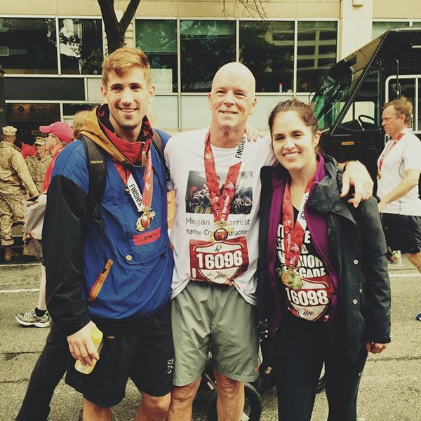 Three runners posing for a photo together after a race, wearing their medals at the finish line.