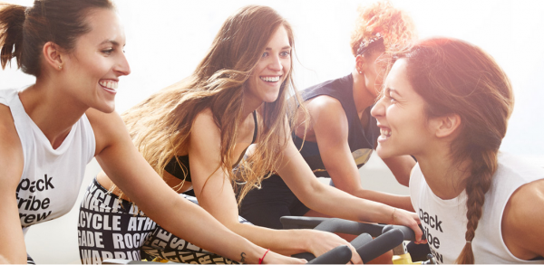 3 women on soul cycle bikes with their coach gladly cheering them on