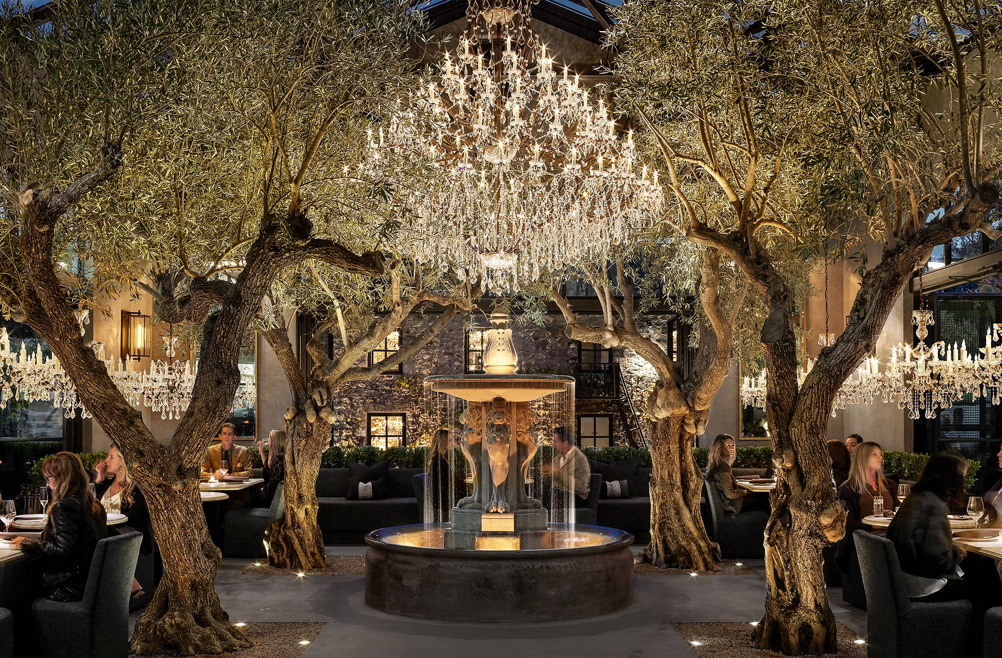 RH garden courtyard lit up at night, with a large fountain, olive trees and chandeliers.