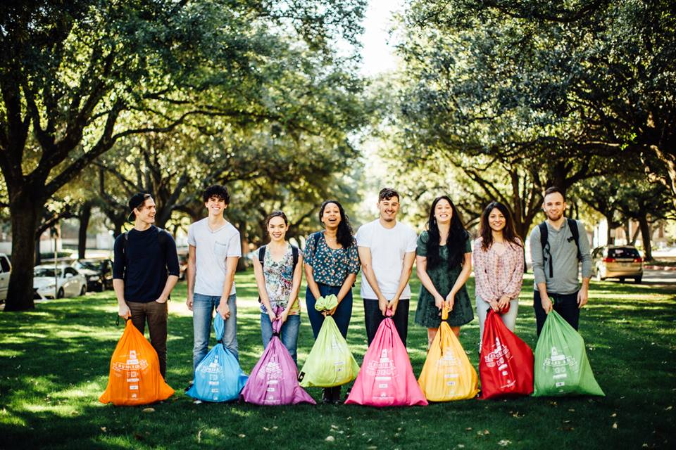 row of young adults holding colorful laundry bags