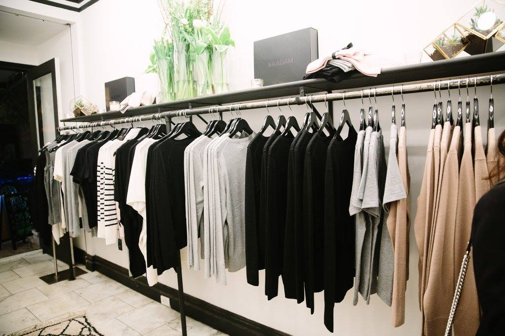 rack of black, white, gray, and nude sweaters in a store