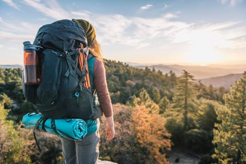 woman with large hiking backpack looking out over landscape of mountains