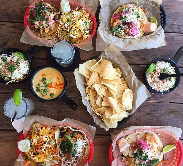 Overhead view of various tacos from Torchy's Tacos on a wooden table.