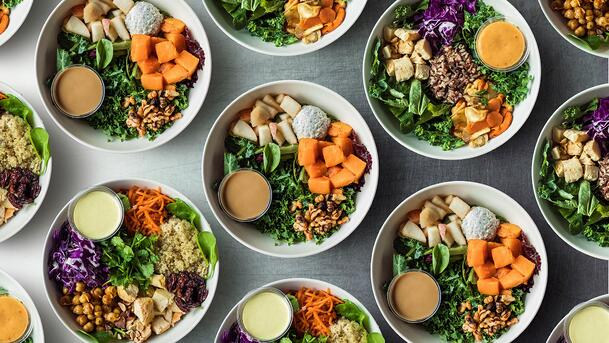 Overhead view of various bowls of healthy salads.