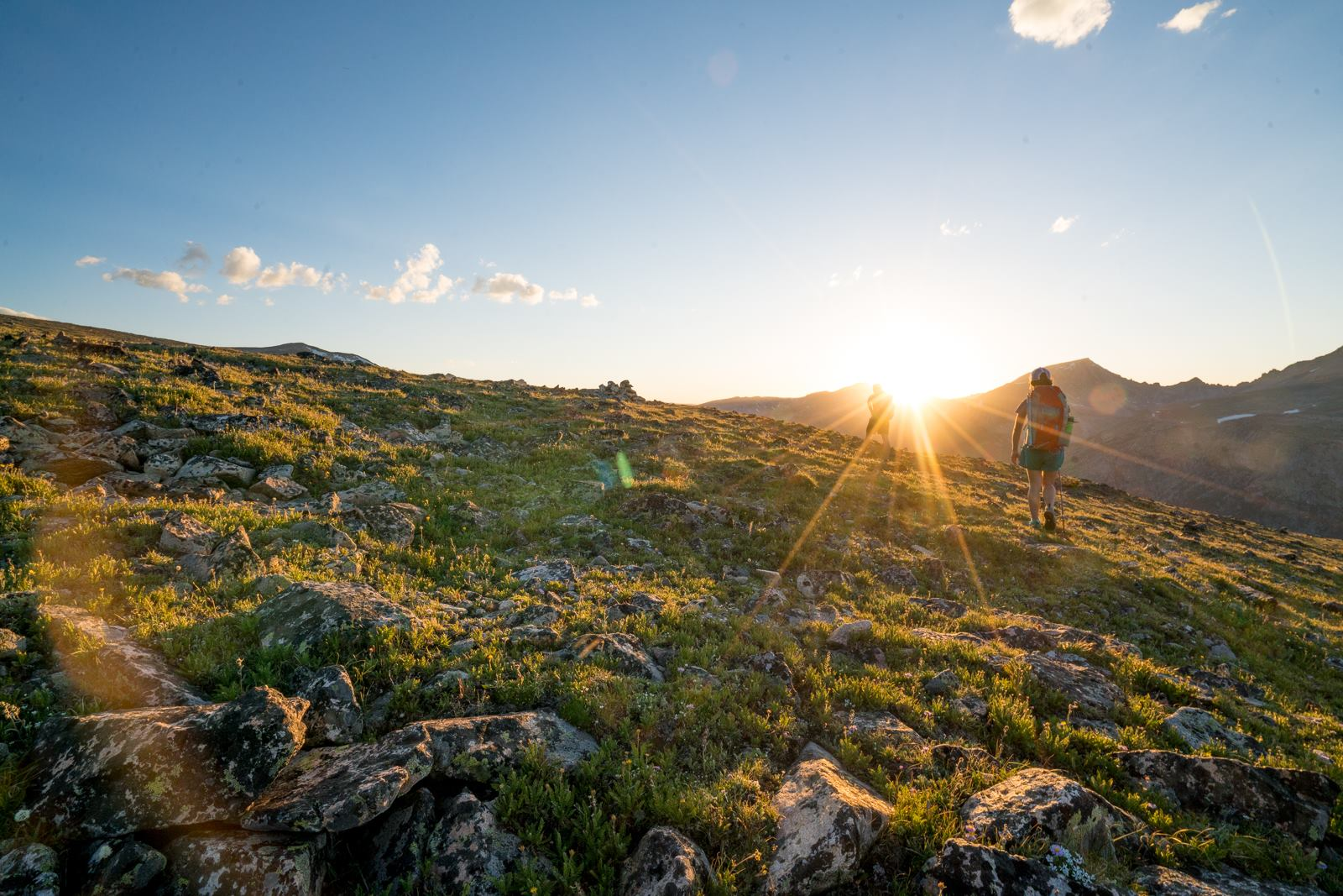 man hiking on a mountain during sunrise
