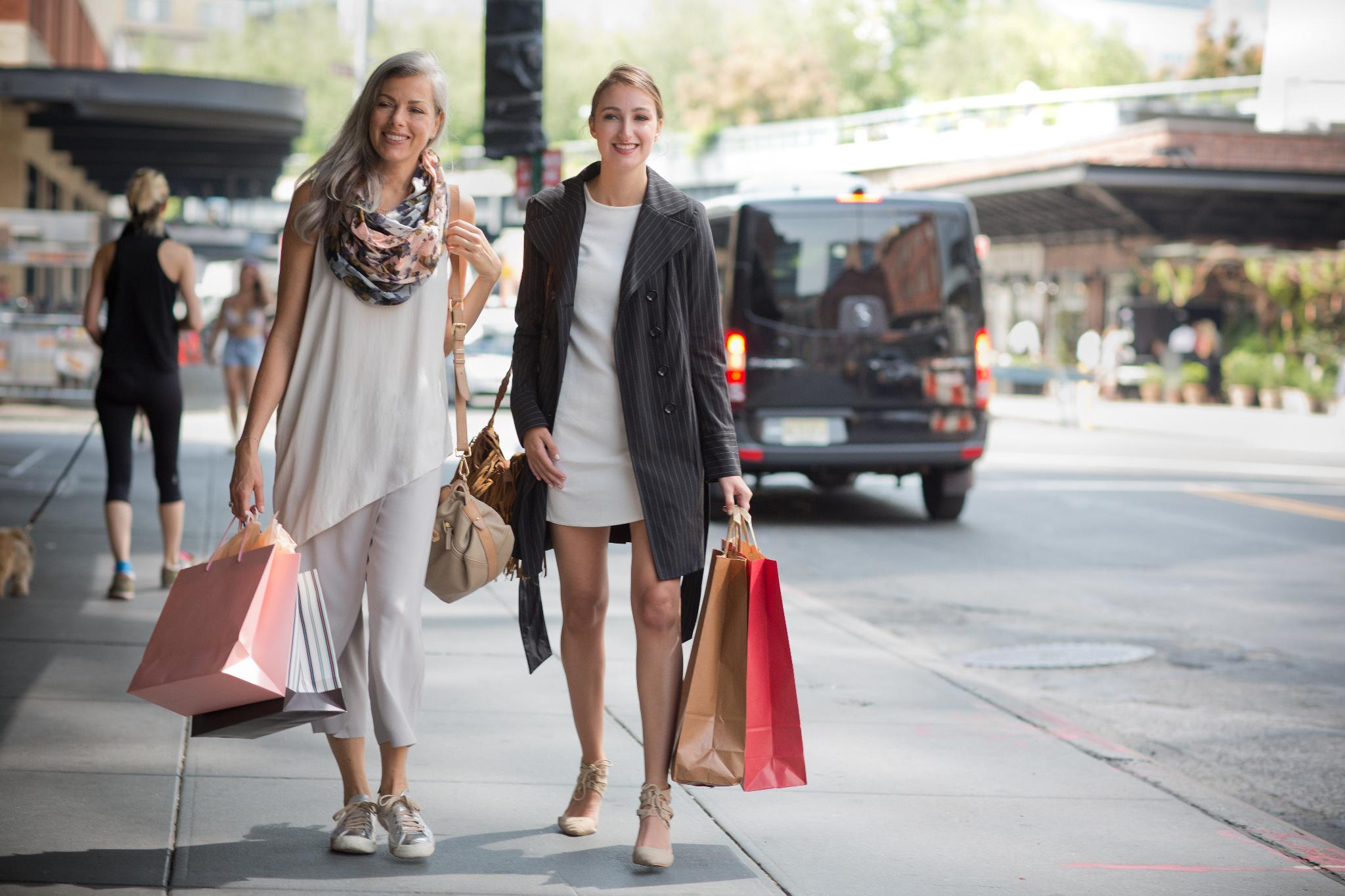 two women outdoors walking the streets holding large shopping bags