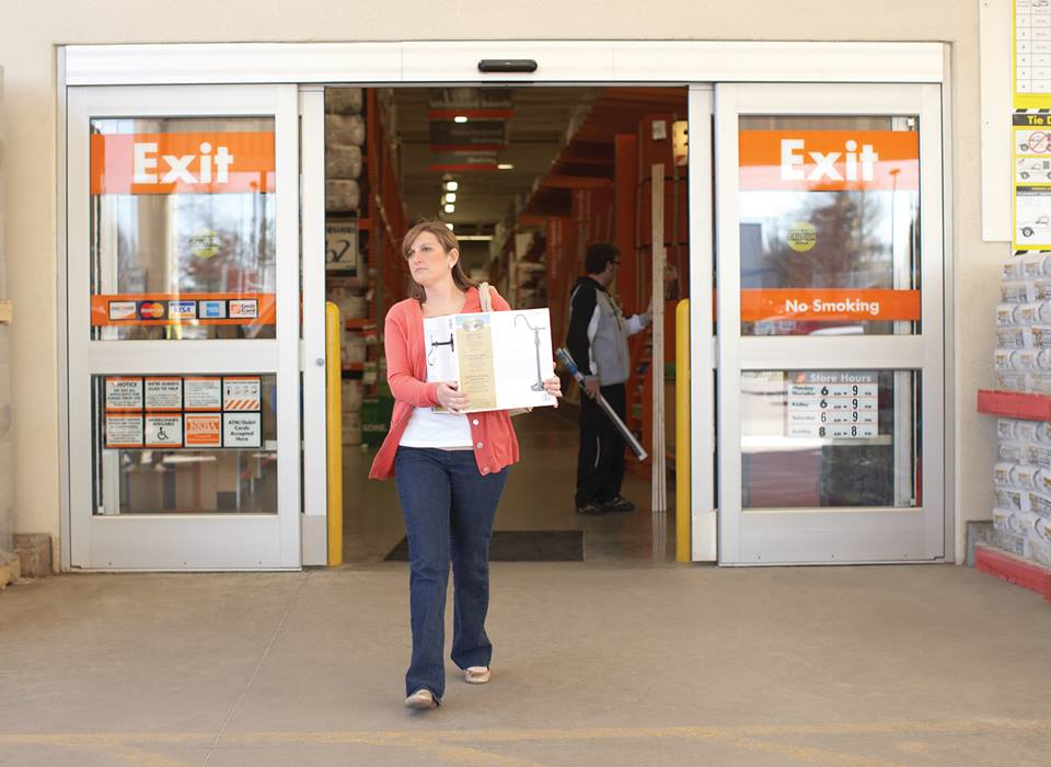 woman carrying out boxes from Home Depot