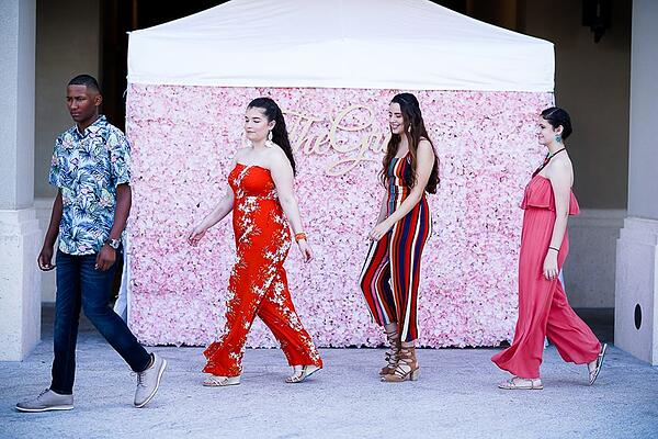 3 women and 1 man walking in front of pink flower wall for The Grove