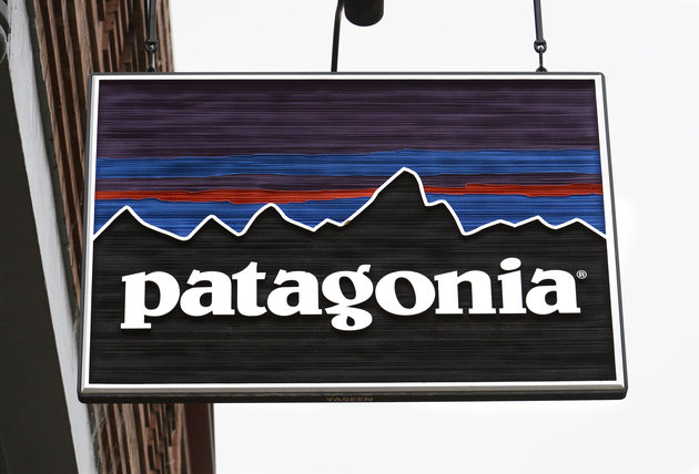 Hanging wooden sign of Patagonia mountain logo.