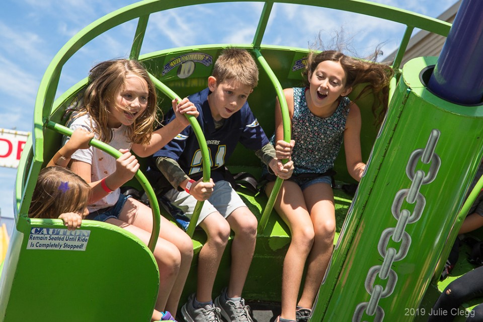 Kids on green spinning style fair ride