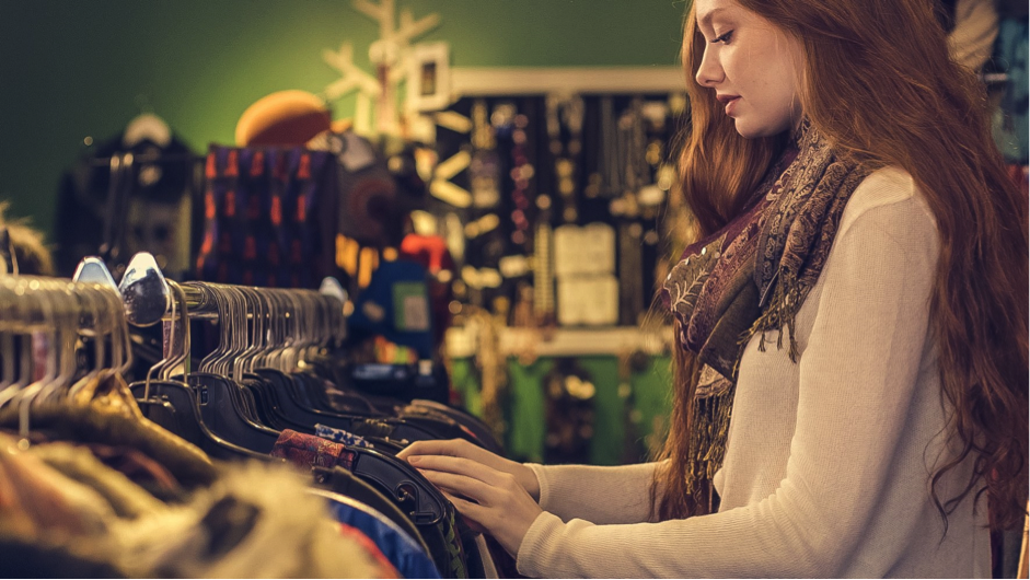 young woman shopping in store looking at rack of clothing