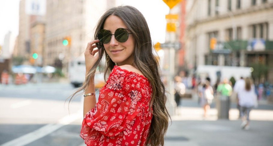 young woman wearing a red paisley top in a busy city