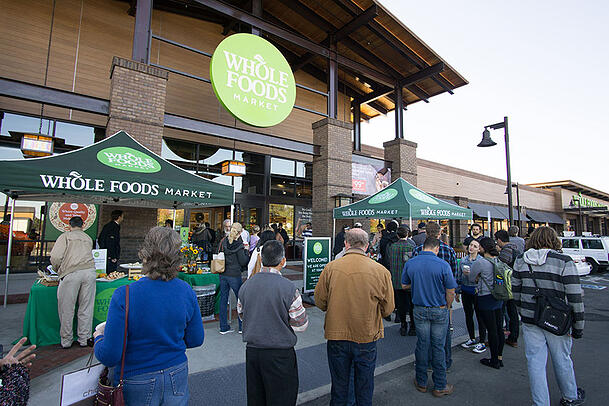 Customers standing around outside at Whole Foods Market grand opening.
