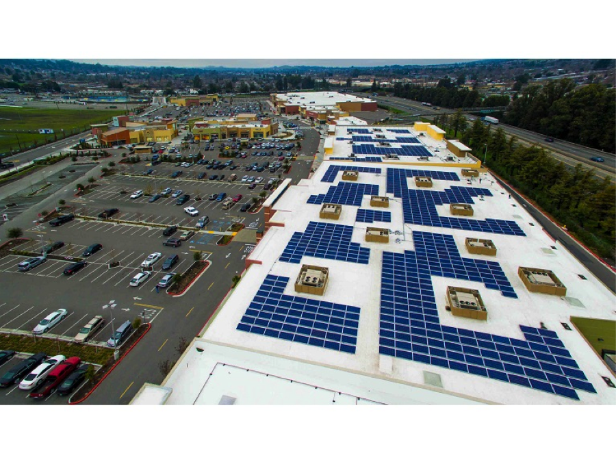 aerial view of solar panels next to a large parking lot.