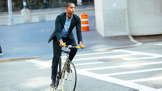 Bicycler in a causal suit riding in a city.