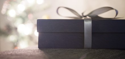 A purple gift box with a silver bow tied around it.