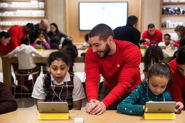 Apple employee showing an iPad to a young girl inside an Apple store.