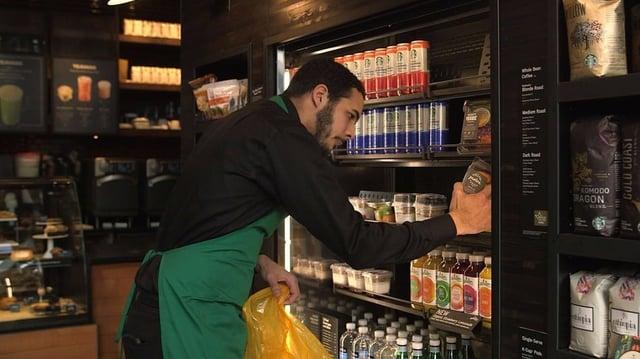Starbucks employee stocking shelves of store refrigerator