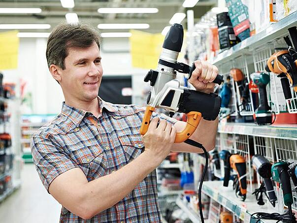 Home Depot customer admiring a power drill.