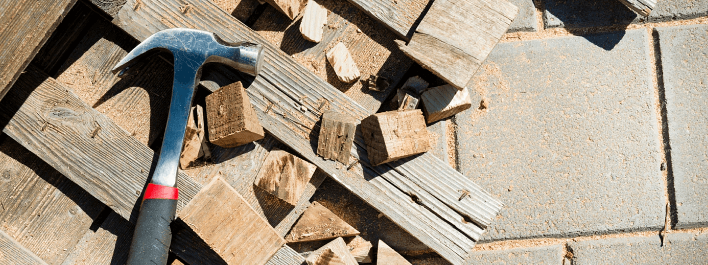 Hammer lying down on scrap wood.