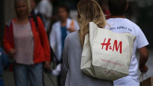 Shopper carrying an H&M shopping bag.