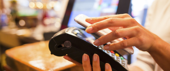 hand holding smartphone next to credit card machine