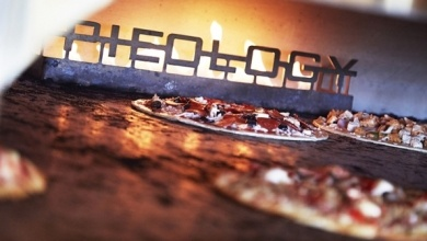 Pizzas in an oven with a three-dimensional metal logo inside the oven that spells out Pieology.