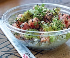 A poke bowl and unopened chopsticks on a table.