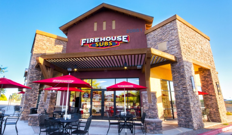 Firehouse Subs storefront with tables and chairs out front.