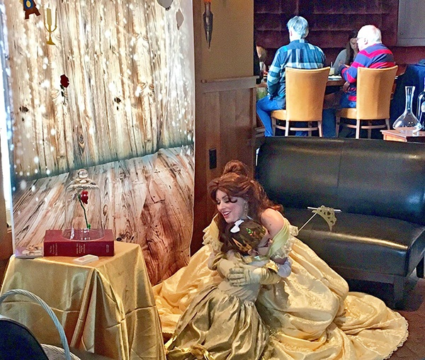 Woman dressed up as Disney's Belle hugging a little girl.