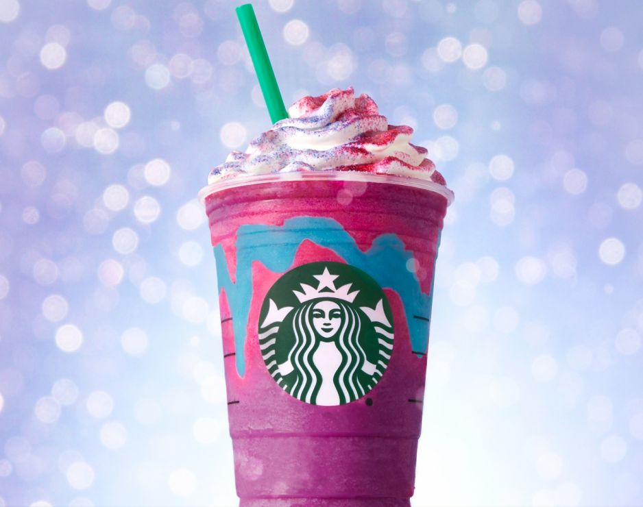 Starbucks purple and pink Unicorn Frappucino with whipped cream and purple and pink sprinkles on top.