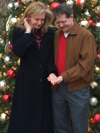 Sherri Johnston & David Wensil looking at engagement ring while standing in front of a Christmas tree.