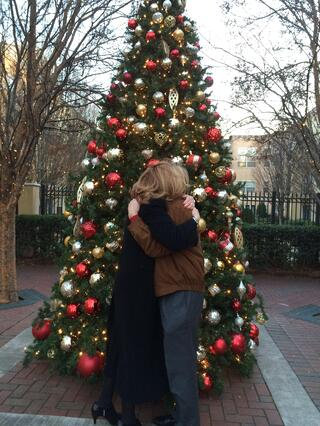 The happy couple hugging in front a large Christmas tree.