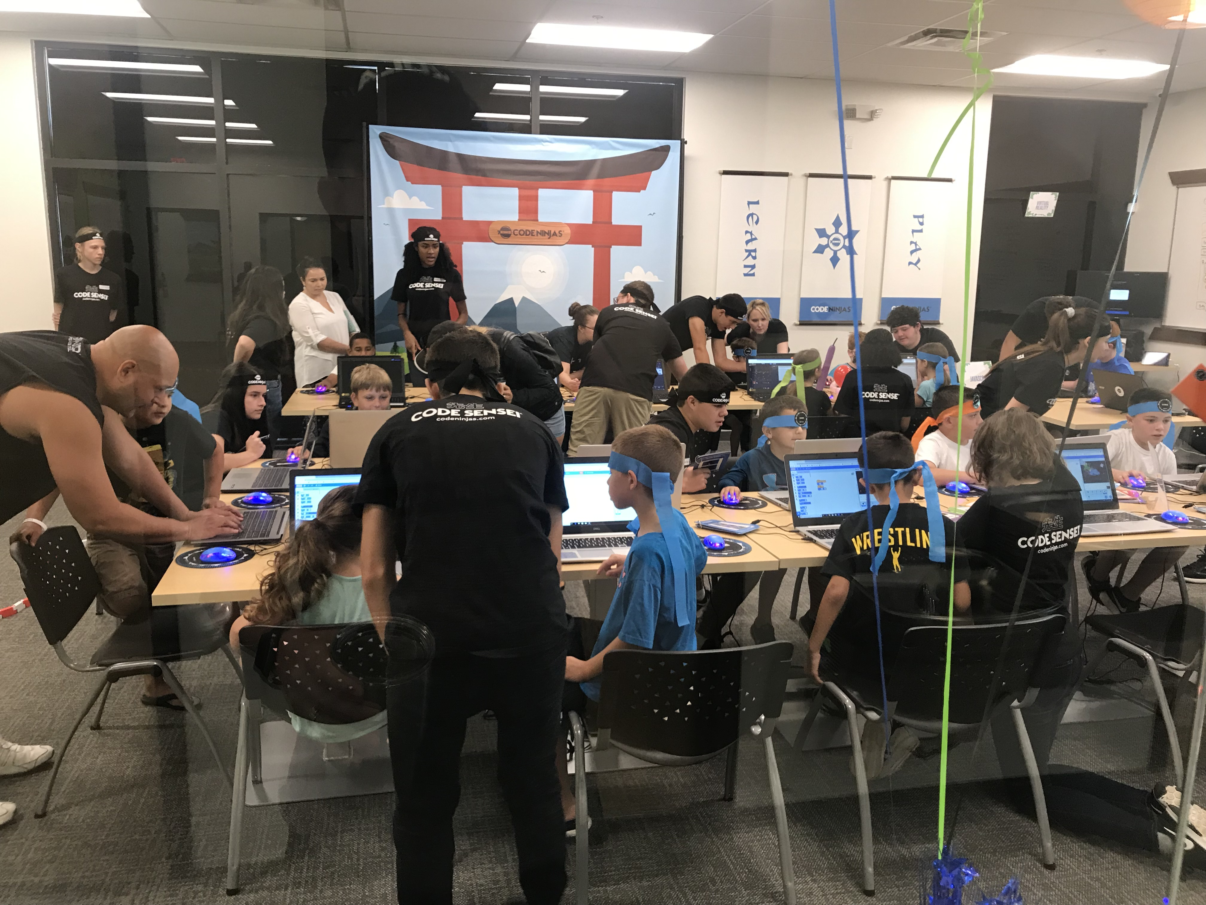 classroom full of kids wearing ninja headbands while using laptops.