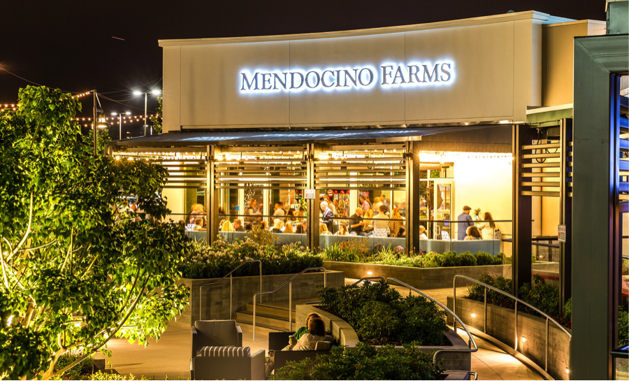 Mendocinio Farms storefront next to outside seating area at night.
