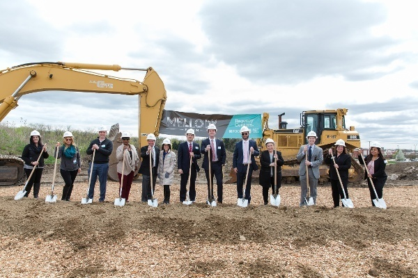 Regency employees holding shovels and wearing hardhats at a groundbreaking ceremony.