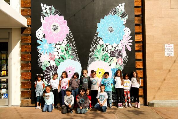 Members of 'Friends at Village at La Floresta' Kids' Club pose in front of butterfly mural
