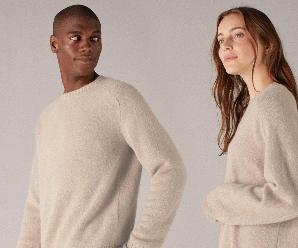 two adults wearing the Naadam sweater in tan