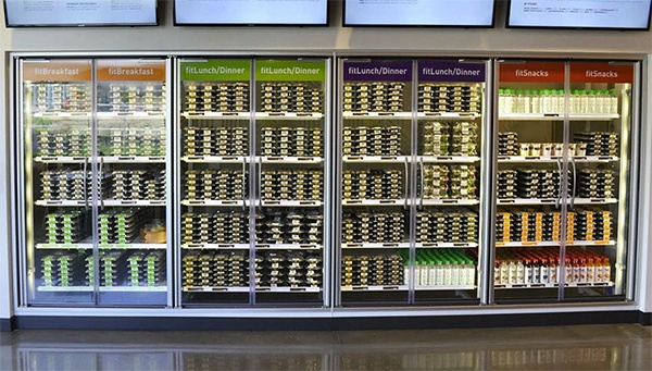 Commercial refrigerators with stacks of prepared Ready Fit Go meals.