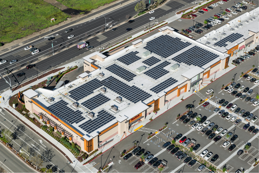 Company building with solar panels on roof surrounded by a large parking lot.