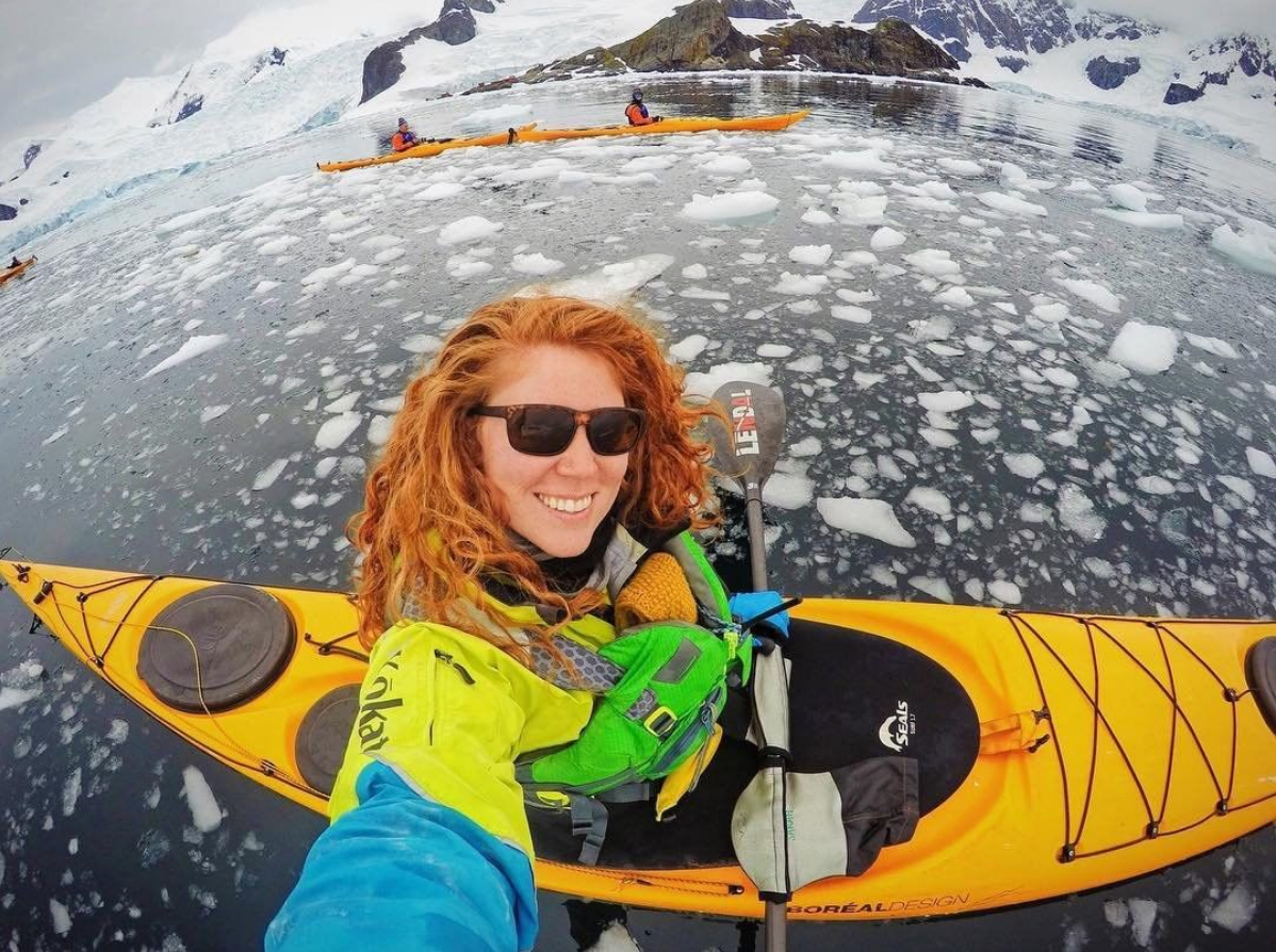 Young woman taking a selfie in a kayak on a frozen lake.